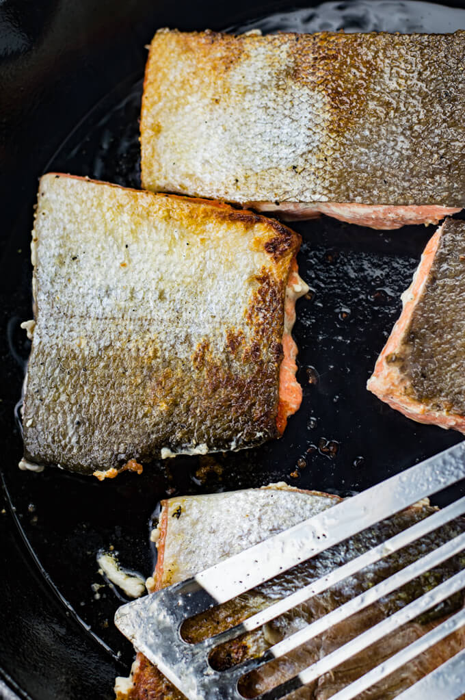Four pieces of salmon are cooking in a black cast iron skillet with the skins up. A Fish spatula sits on top of them.