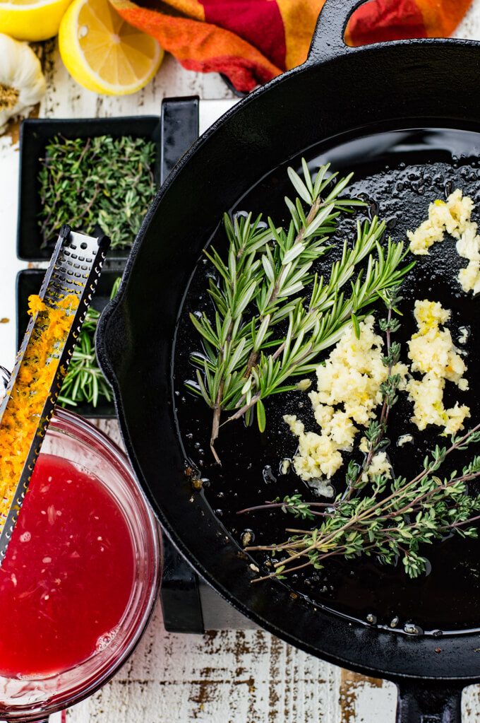 Sprigs of thyme and rosemary along with minced garlic are in a black cast iron skillet. A red and orange napkin, small bowls of thyme and rosemary, a bowl of blood orange juice sit next to the skillet. A zester with blood orange zest rests on top of the bowl.