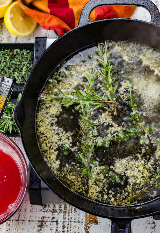 Thyme, Rosemary and garlic simmers in white wine in a black cast iron skillet. A red and orange napkin, small bowls of thyme and rosemary and a bowl of blood orange juice sit next to the skillet.