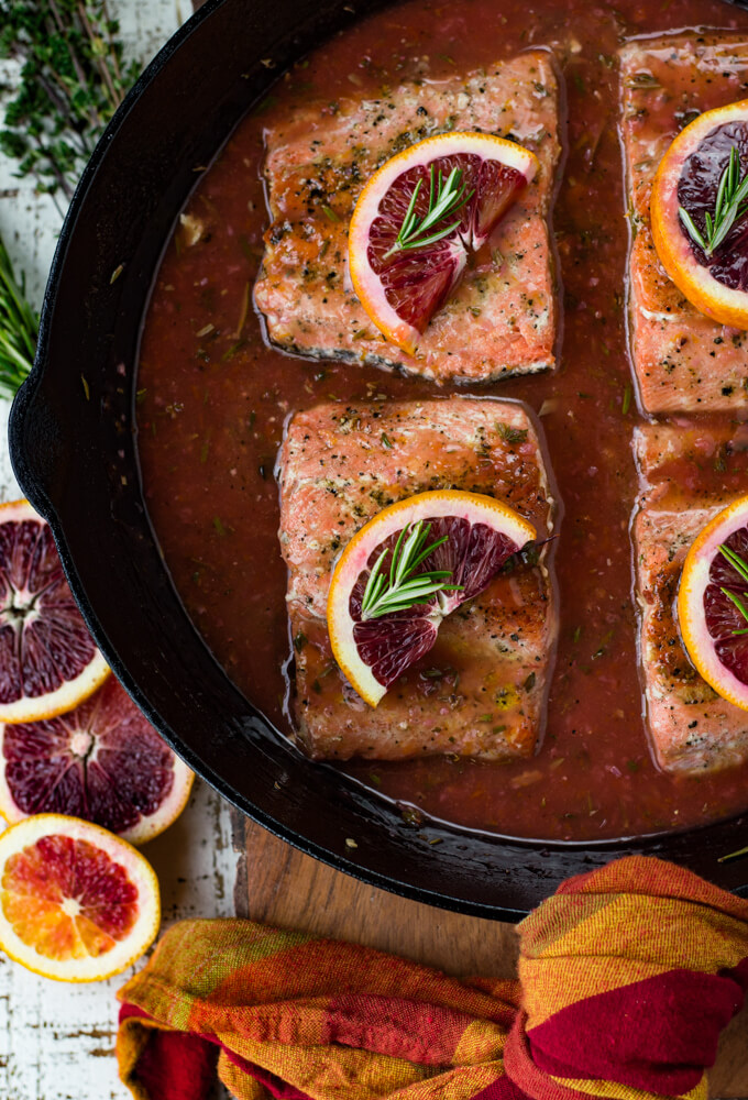 Black cast iron skillet with pieces of salmon sitting in a blood orange sauce. Each salmon has a half slice of blood orange and a small sprig of rosemary on top. Slices of blood oranges and herbs sit next to the pan.