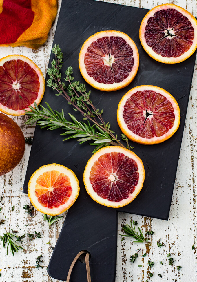 Five slices of blood oranges sit on a black cutting board with sprigs of thyme and rosemary next to them. A red and orange napkin and two halves of a blood orange sit next to the cutting board.