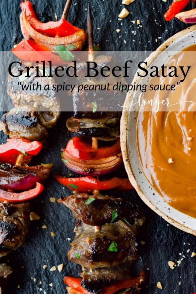 Flank steak, red onions and red bell peppers on wooden skewers with a bowl of peanut sauce next to them.