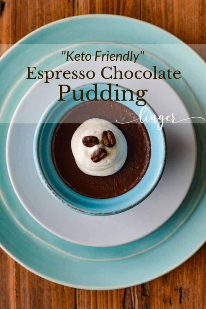 A bowl of chocolate pudding in a blue ramekin on a white sauce and a blue plate.
