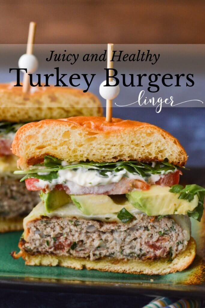 A turkey burger cut in half with the cut sides showing. The burger has avocado slices, tomato and arugula.