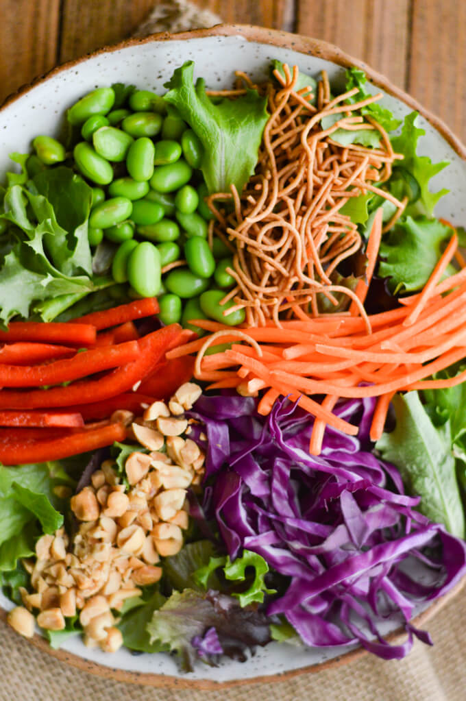 A bowl of salad with edamame, red cabbage, peanuts, red peppers and rice noodles.