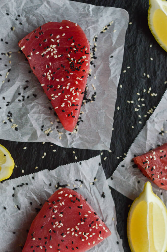 3 uncooked ahi tuna steaks with black and white sesame seeds on parchment paper with wedges of lemons scattered around.