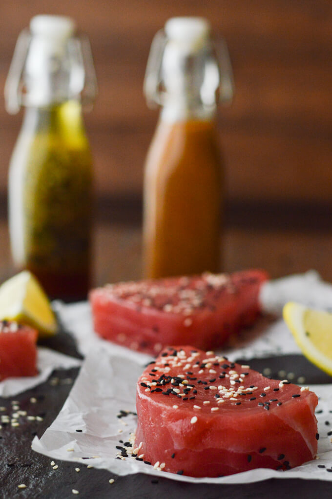 3 uncooked ahi tuna steaks on parchments paper with lemon wedges around. A bottle of Asian vinaigrette and a bottle of peanut sauce are in the background.