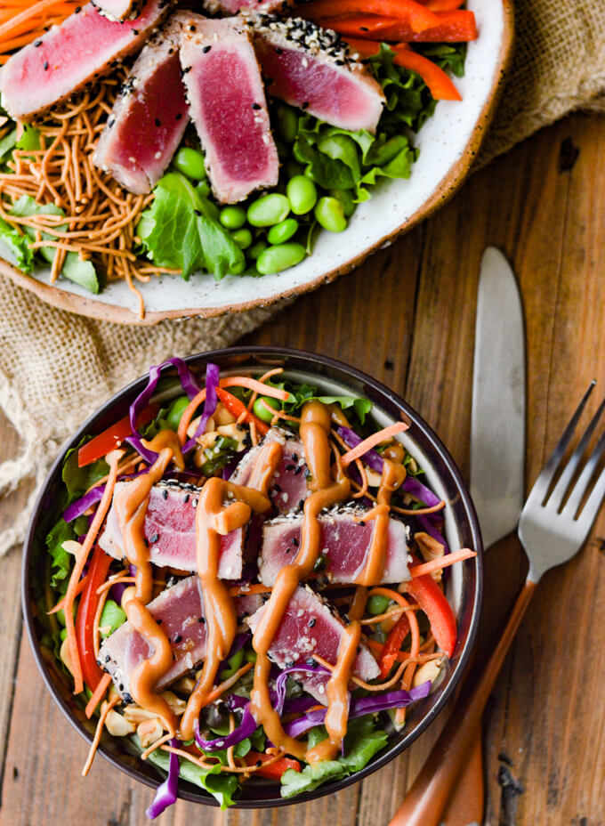 An asian salad with seared ahi tuna on top and peanut sauce drizzled on top. Another bowl of salad next to it with a knife and a fork.