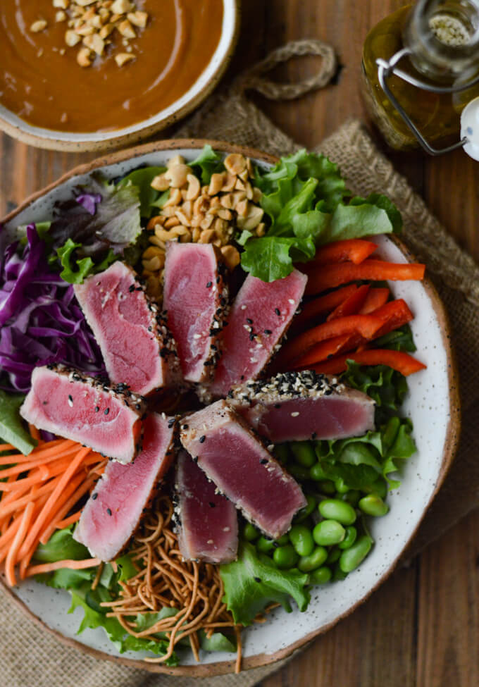 A bowl of salad with seared tuna, edamame, red cabbage, peanuts, red peppers and rice noodles with a bowl of peanut sauce next to it.