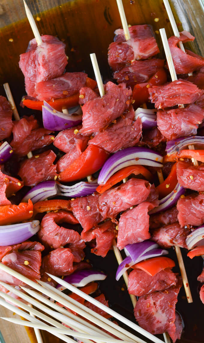 Flank steak, red onion and red bell peppers on wooden skewers sit in a glassware pan with marinade.