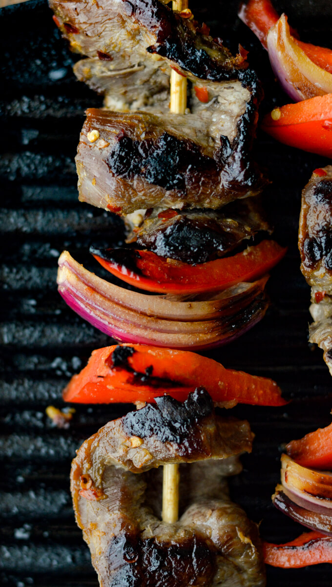 A closeup view of flank steak, red onions, red bell peppers on wooden skewers are on an Electric Grill.