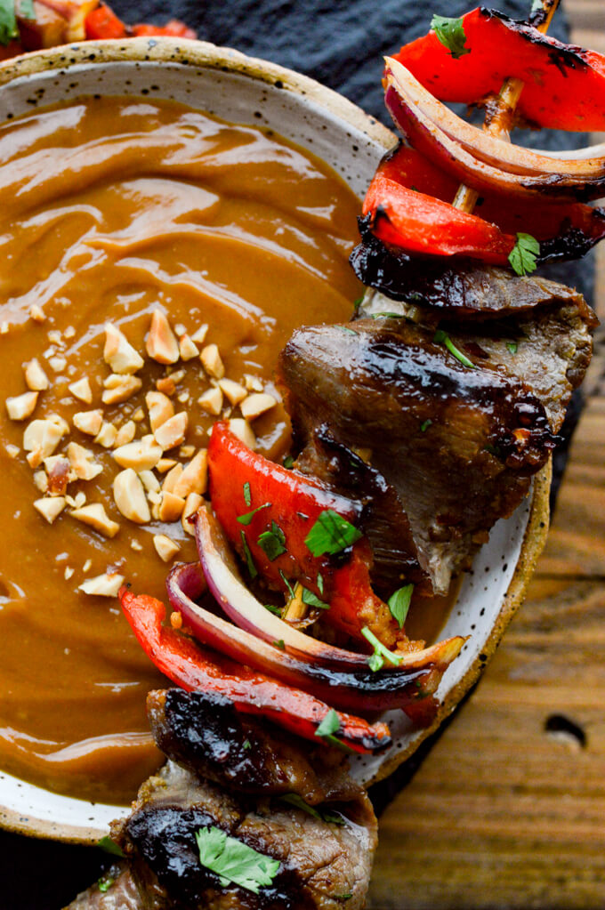A closeup photo of a bowl of peanut sauce with a flank steak skewer sitting on the bowl.