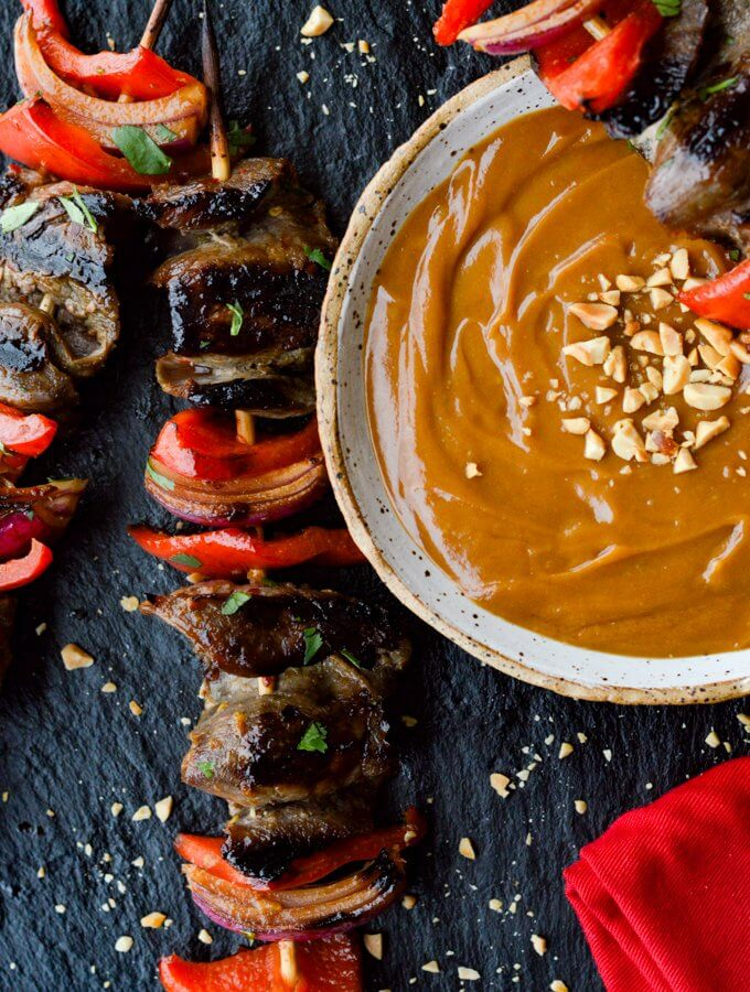 A bowl of peanut sauce with 2 beef satay skewers next to it.