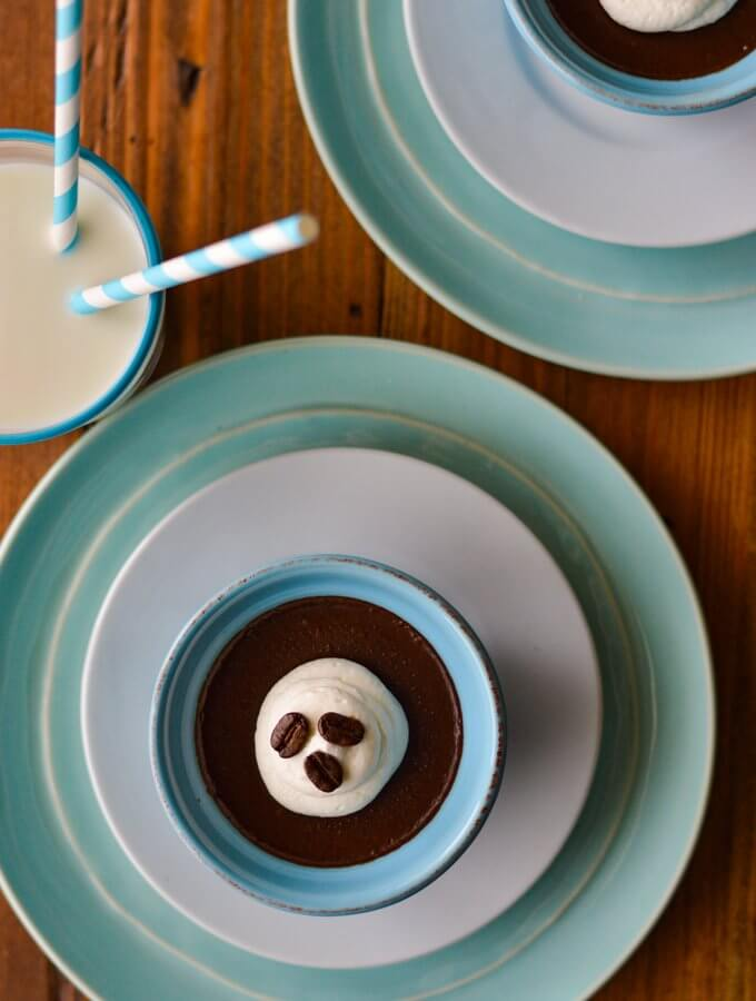 A bowl of chocolate pudding in a blue ramekin on a white sauce and a blue plate with a glass of milk and blue and white striped straw.