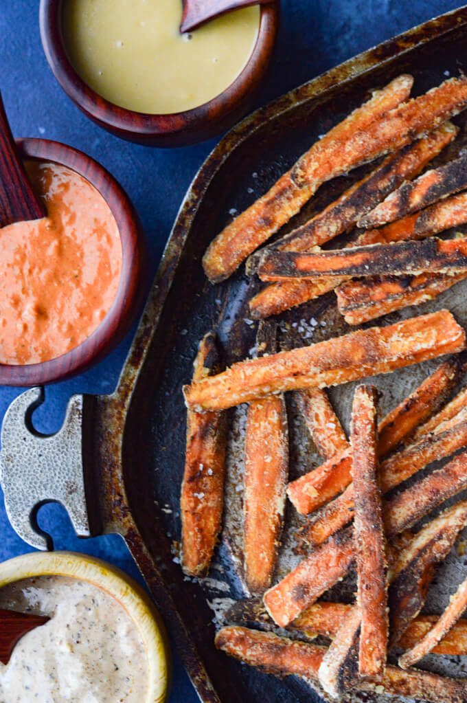 Baked Sweet Potato fries on a pan with 3 different dipping sauces.