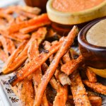 A platter of baked sweet potato fries with 3 bowls of dipping sauce sits next to them.