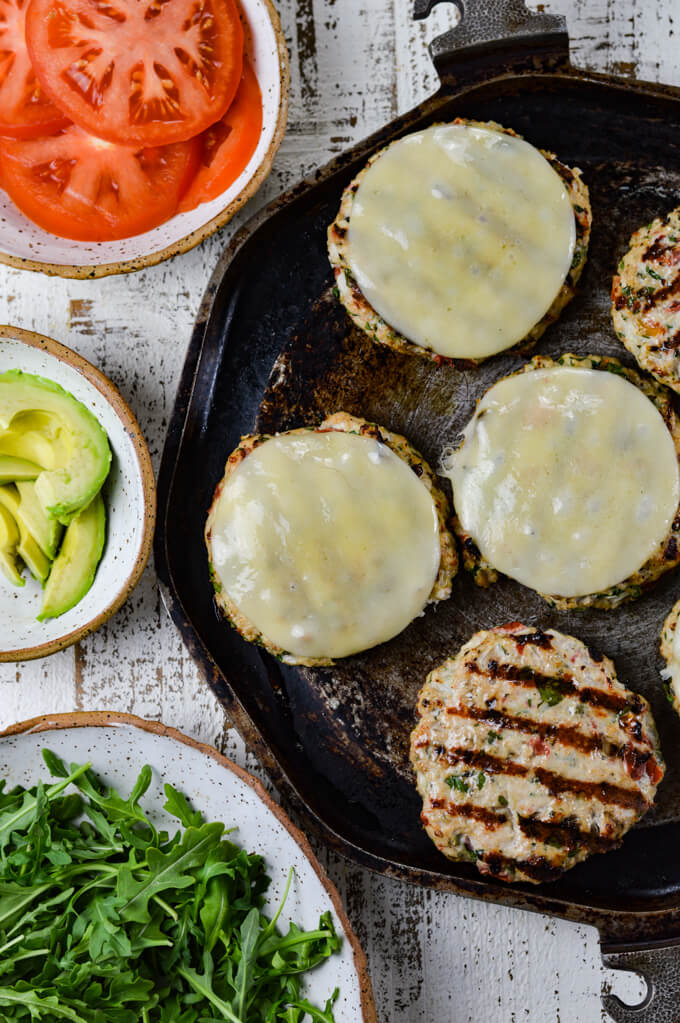 Five grilled turkey burgers. Three have provolone cheese on them. Bowls of sliced tomatoes, sliced avocados and arugula lettuce sits beside them.