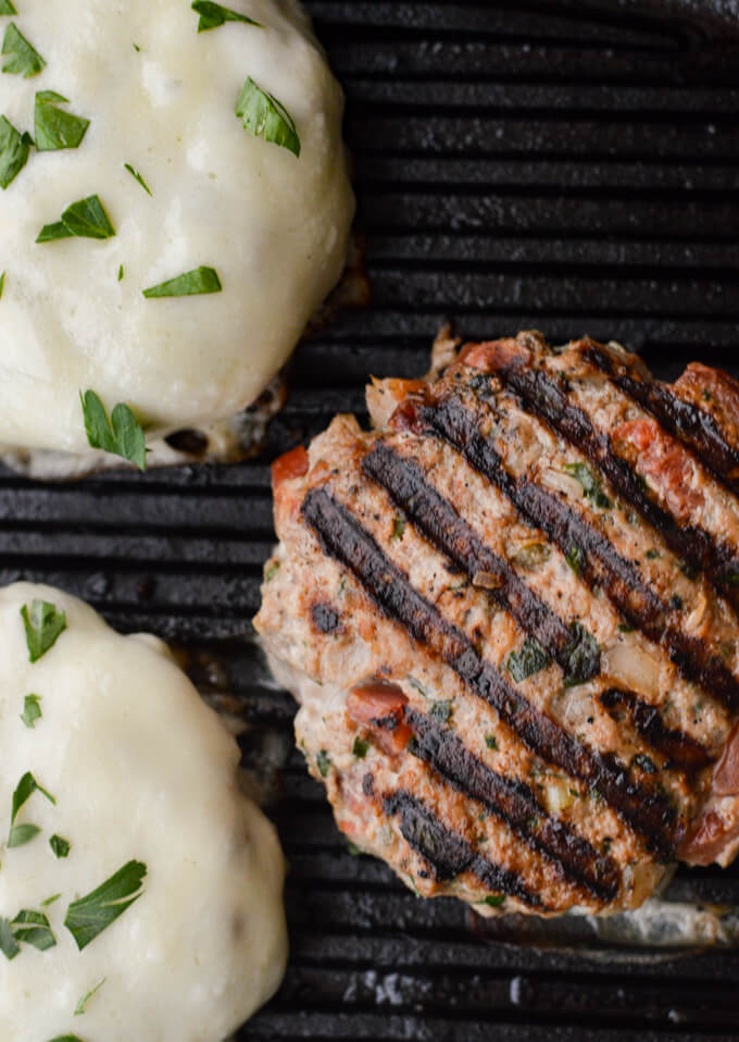A closeup view of three turkey burgers frying in a cast iron skillet. Two have provolone cheese slices with chopped parsley sprinkled on them.