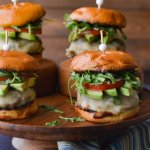 A front view of four turkey burgers with avocado slices, tomato and arugula sitting on a wooden tray with a blue striped napkin in front.