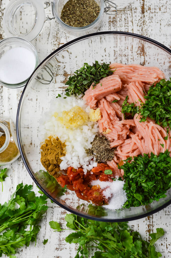 A clear mixing bowl of ground turkey, fresh chopped herbs, rotel tomatoes, spices, chopped onions and garlic. Seasonings and herbs sit next to the bowl.