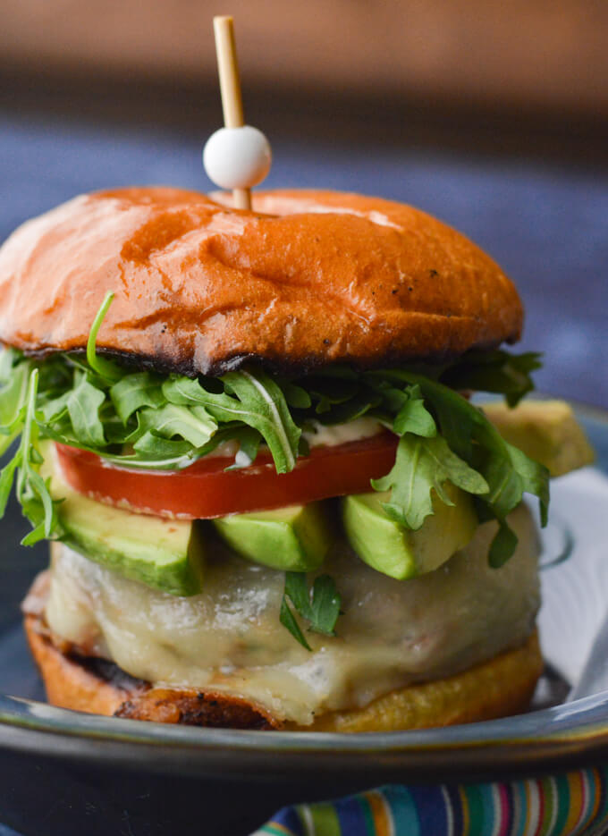 A front closeup view of a turkey burger with avocado slices, tomato and arugula.