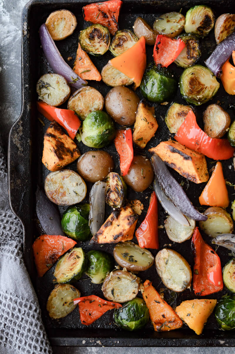 A pan of roasted vegetables - red potatoes, sweet potatoes, butternut squash, Brussel sprouts, red onion, red bell pepper.
