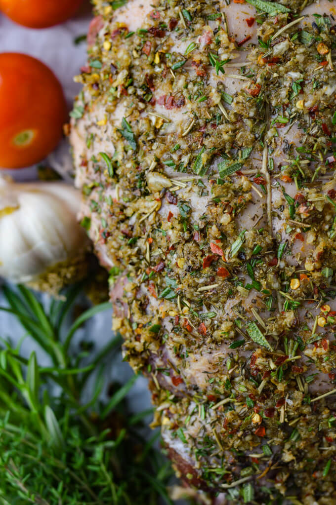 A close up photo of a raw leg of lamb with a garlic and herb rub on it. Tomatoes, garlice and fresh herbs sit next to it.