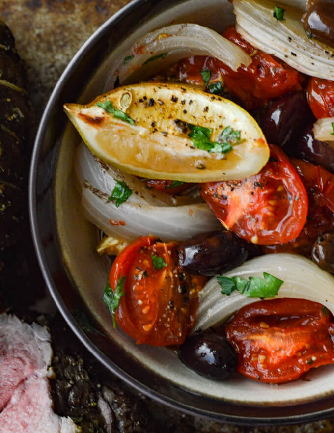 A bowl of roasted tomatoes, onions, lemon wedges and kalamata olives.