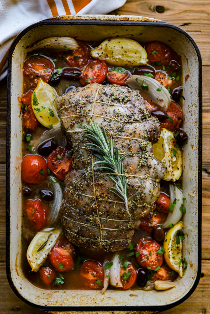 A roasted leg of lamb in a pan tied with string and a sprig of rosemary. Roasted tomatoes, onions, kalamata olives and lemon wedges are scattered around the lamb.