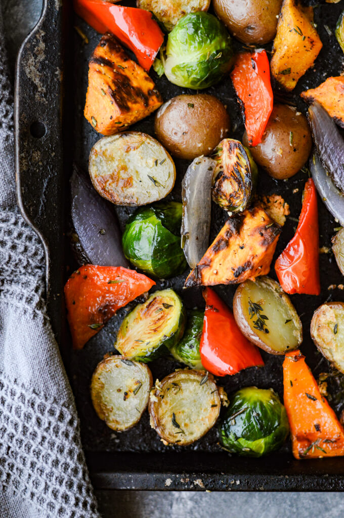 A pan of roasted potatoes,sweet potatoes, butternut squash, red peppers, Brussel Sprouts, and Red onions.