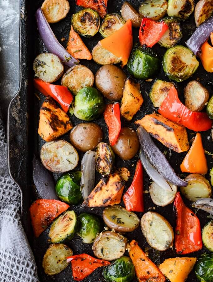 A pan of roasted potatoes,,sweet potatoes, butternut squash, red peppers, Brussel Sprouts, and Red onions.