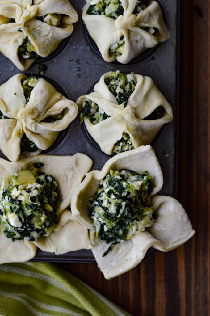 Spinach and Feta Puff Pastry Appetizers - raw in mini muffin tins with a green and white napkin beside it