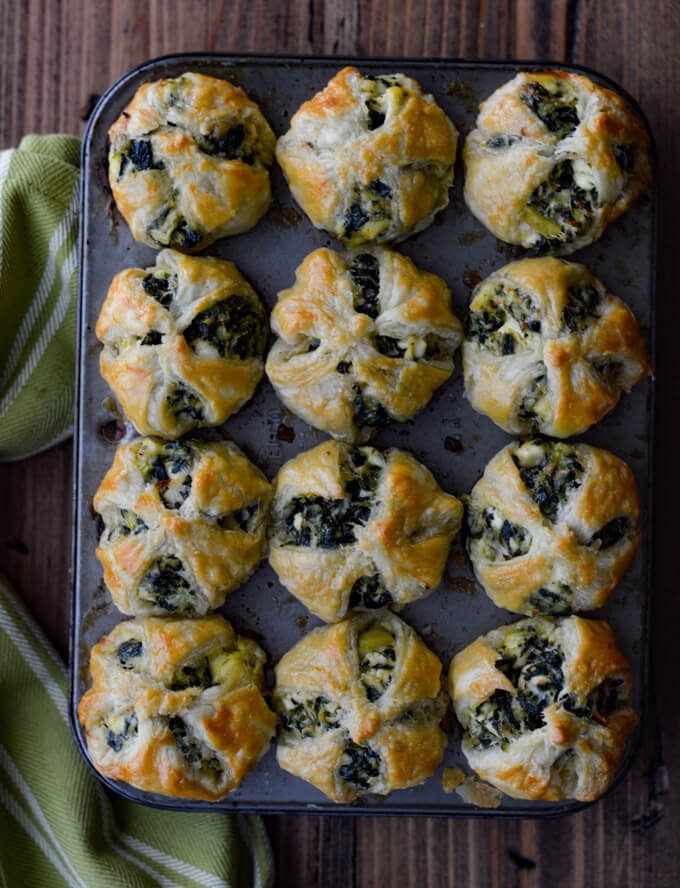 Cooked Spinach and Feta Puff Pastry Appetizers in mini muffin tins with a green and white napkin beside it