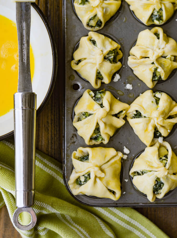 Spinach and Feta Puff Pastry Appetizers - unbaked in mini muffin tins with egg wash on them a green and white napkin beside it and a bowl of egg wash