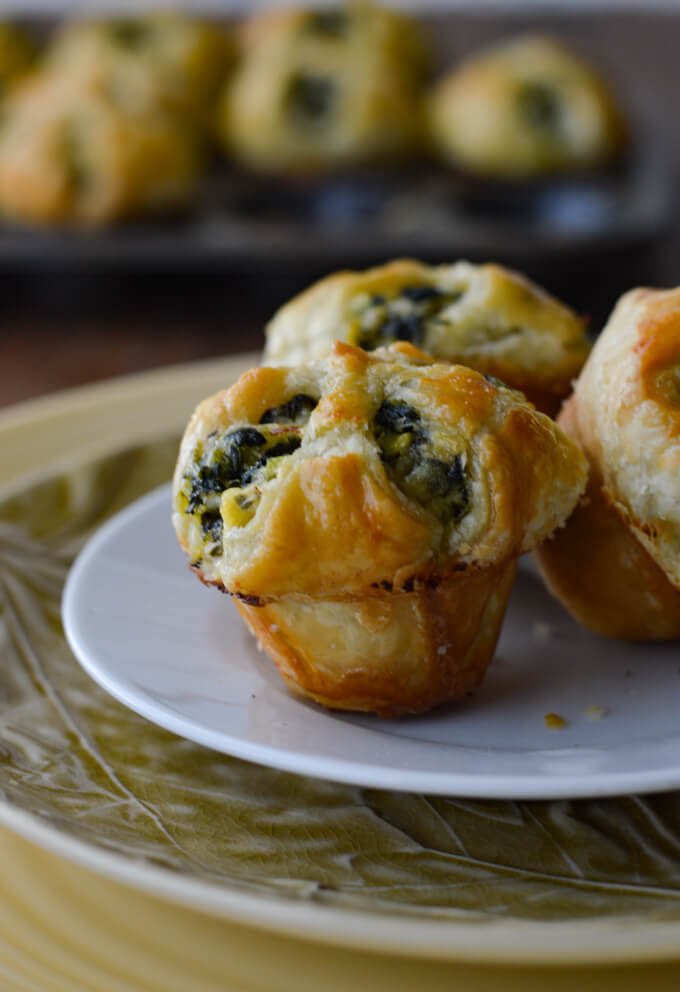 Three Spinach and Feta Puff Pastry Appetizers on a white plate and two other larger plates with a pan of the appetizers in the background.