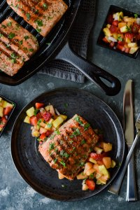 Pan Seared Sockeye Salmon with Fruit Salsa - Plated cooked sockeye salmon sitting on fresh fruit and cooked salmon in a cast iron skillet