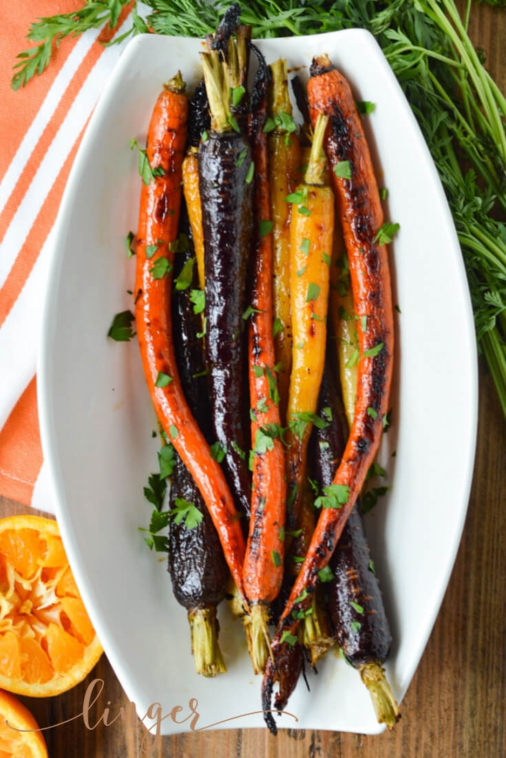 These rainbow candied carrots are bathed in a syrup made from fresh orange juice, pure maple syrup, and bacon grease. They are roasted to a perfect tenderness. And the recipe is a healthy veggie side dish. #candiedcarrots #carrots #veggiesidedish #sidedish #veggies #healthyrecipe #easyrecipe