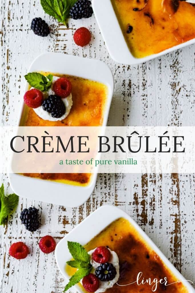 Three creme brulee with fresh fruit on a white surface with fresh berries and mint leaves scattered around.