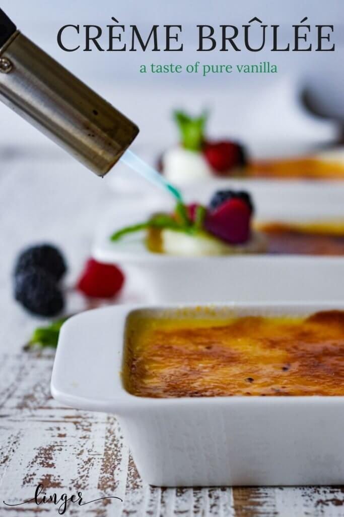 Three baked creme brulee ramekins with a torch caramelizing the sugar. Two are in the background with fresh fruit.