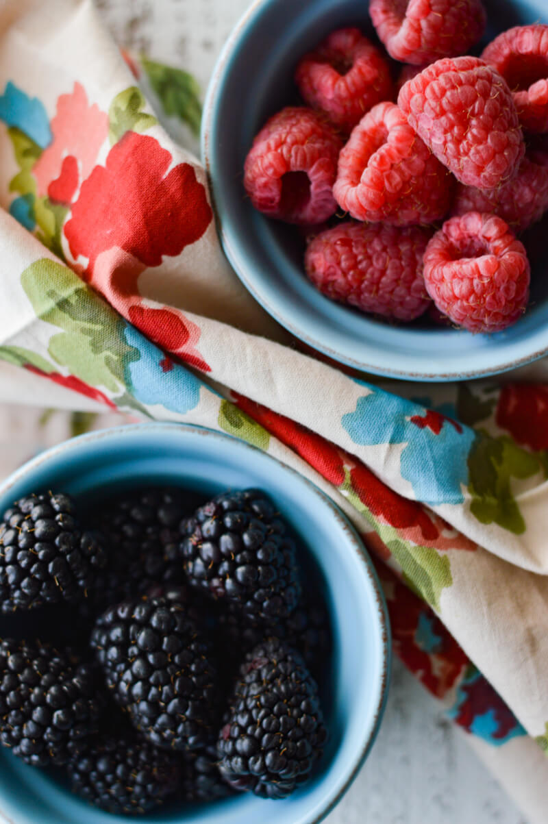 2 small blue bowls, one filled with raspberries and the other filled with blackberries.