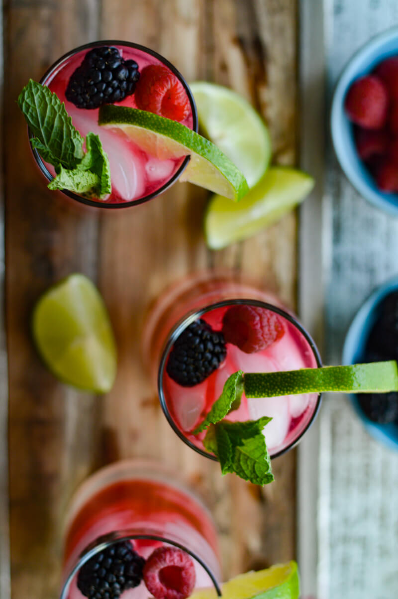 Above photo of 3 glasses of berry infused mojitos on a wooden tray with lime wedges scattered around.