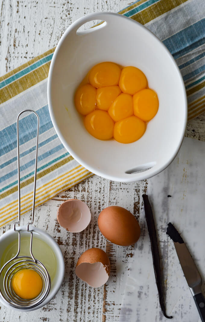 A white bowl of egg yolks with a couple whole brown eggs beside it. A small prepping bowl with egg whites and an egg separater sitting on it. A vanilla bean with a knife and vanilla seeds. All this is sitting on a blue, white and yellow napkin.