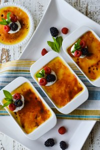 Classic Creamy Creme Brulee with Fresh Fruit on a white background