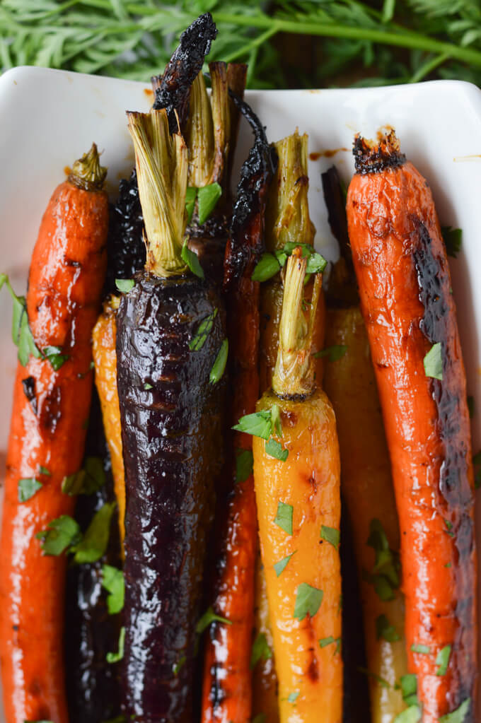 A closeup photo of roasted rainbow carrots in a white dish with fresh parsley sprinkled on top.