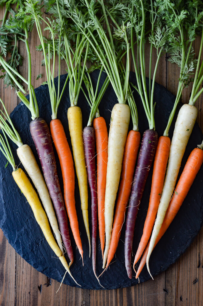 Raw whole rainbow carrots with green leafy stems on a black round cutting board.