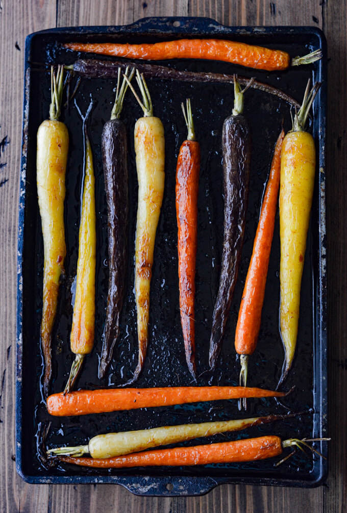 A pan of cooked rainbow carrots on a cookie sheet.