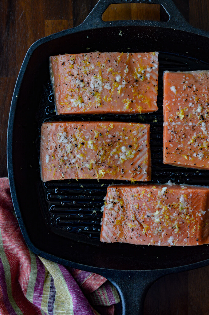 Raw salmon fillets cooking in a cast iron griddle skillet.