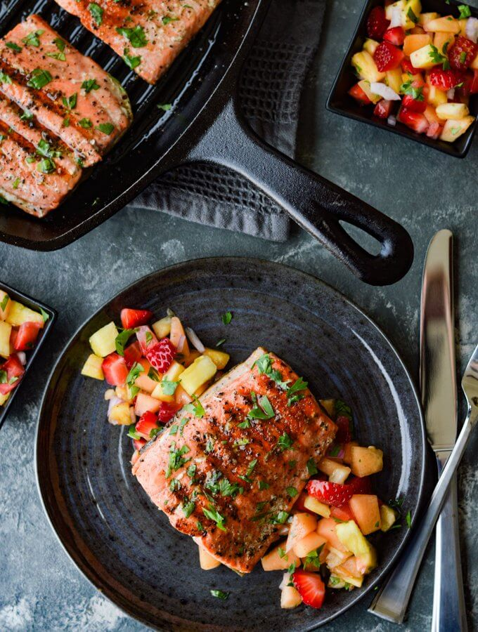 Pan Seared Salmon on a bed of fruit salsa on a charcoal color plate and a cast iron skillet next to it.