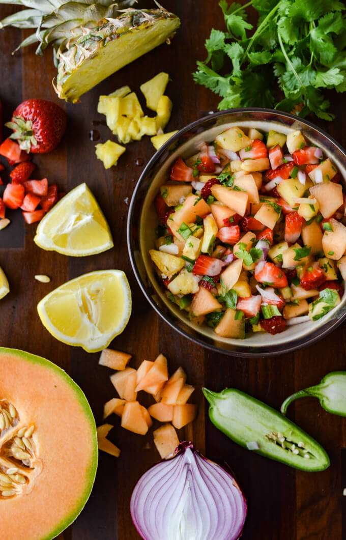 A bowl of fruit salsa with chopped fruit scattered around it.