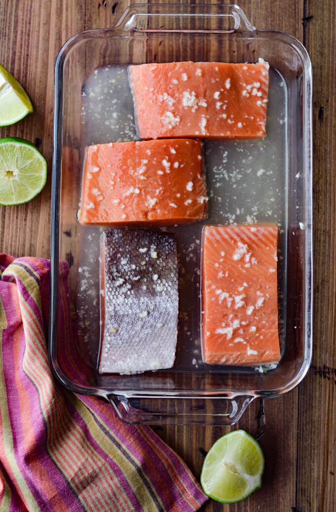 Raw salmon fillets marinating in a glass pan with lime halves and a colorful napkin beside it.